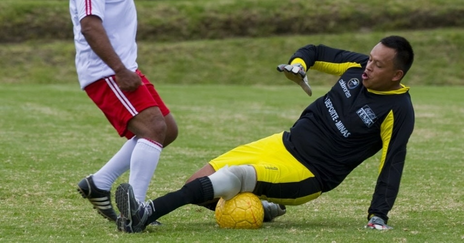 Ex-jogador colombiano Willintong Ortiz tenta passar pelo goleiro Valencia durante amistoso contra time formado por vtimas de minas terrestres, em evento organizado para promover o Mundial Sub-20 em Bogot