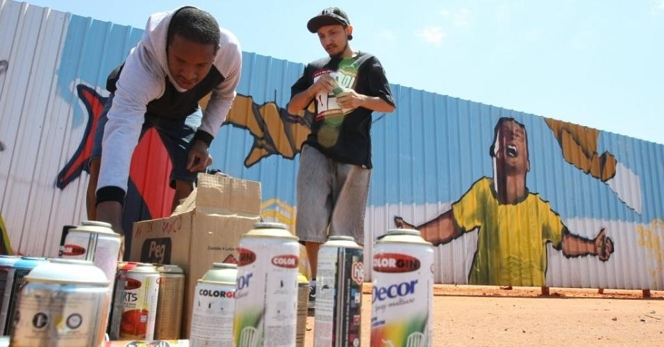 Imagem de grafiteiros preparando um painel nos tapumes da obra do Mané Garrincha, em Brasília