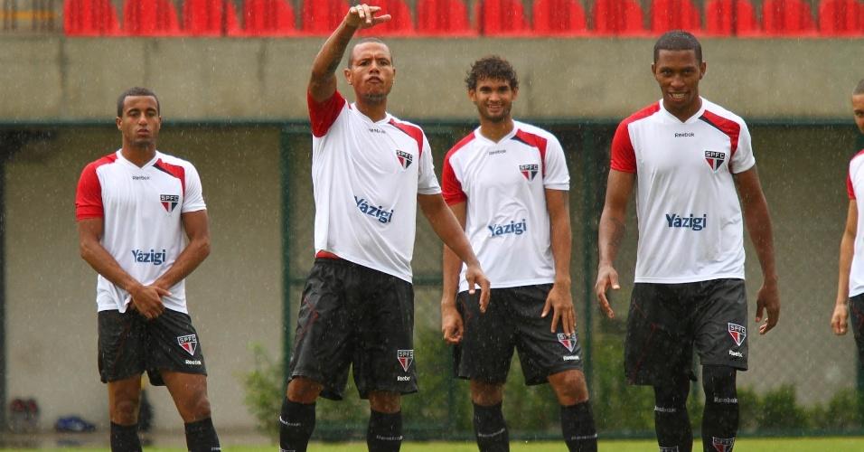 Mesmo sob chuva, Lucas (e), Luis Fabiano e os outros jogadores do São Paulo treinaram forte no CT de Cotia