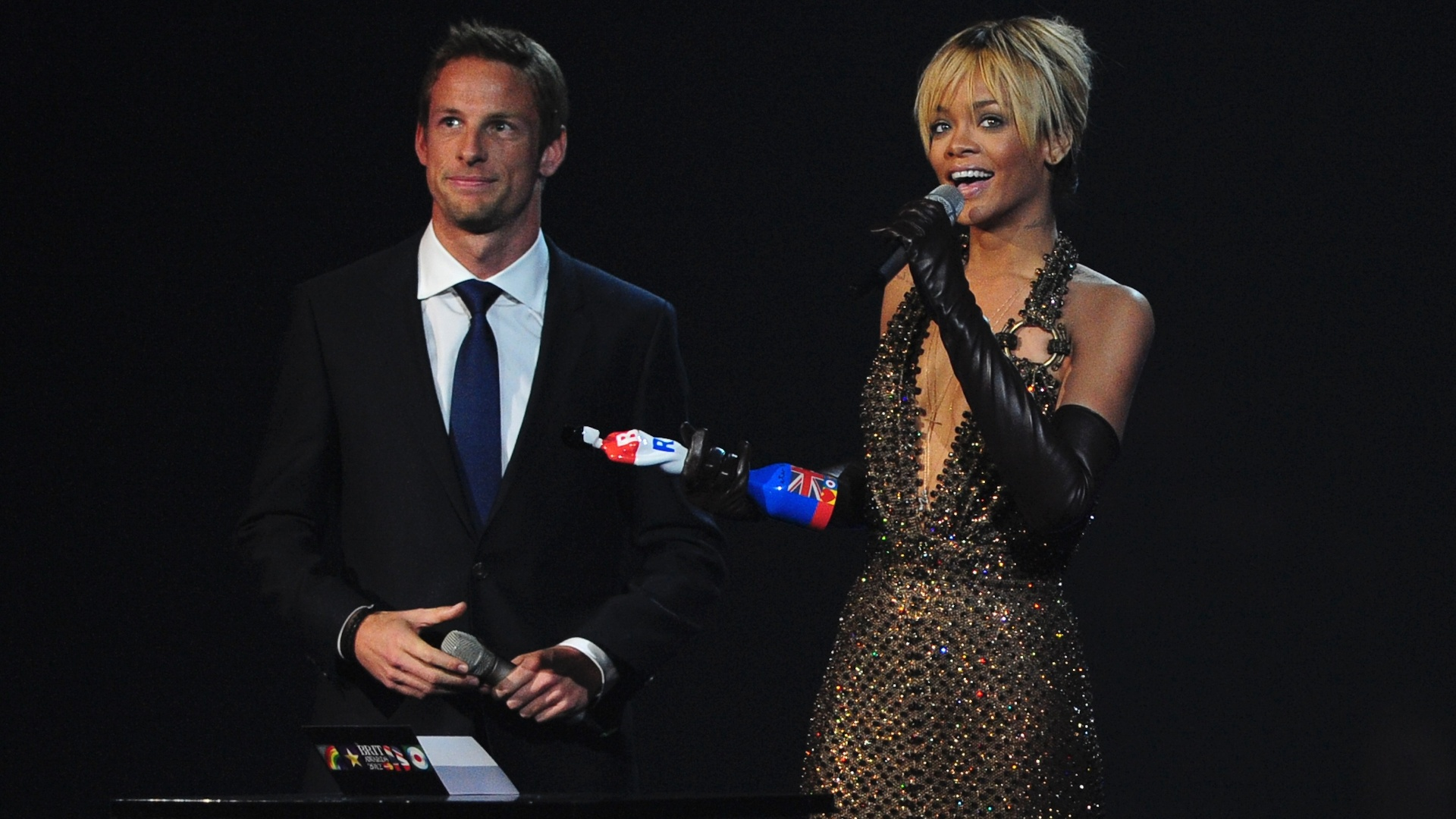 Rihanna recebe prmio das mos do piloto Jenson Button durante o Brit Awards (21/02/2012)