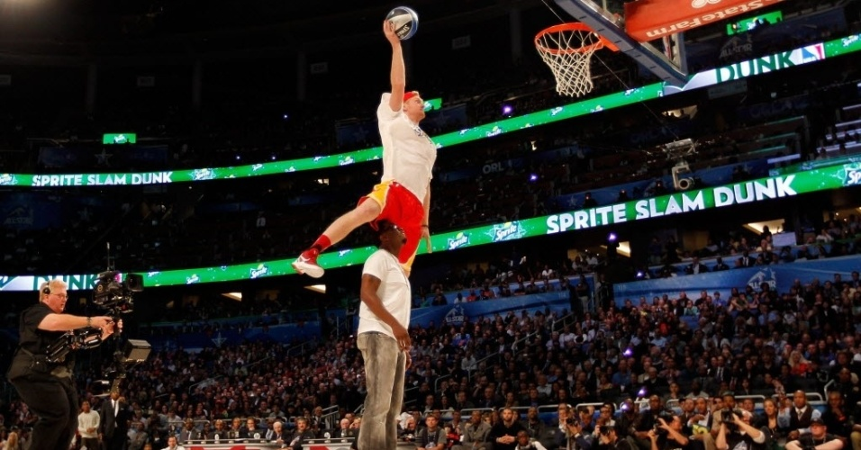 Chase Budinger, do Houston Rockets, salta sobre o rapper P. Diddy durante o Concurso de Enterradas