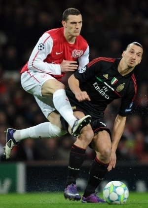 O defensor do Arsenal, Thomas Vermaelen, marca o artilheiro do Milan, Zlatan Ibrahimovic