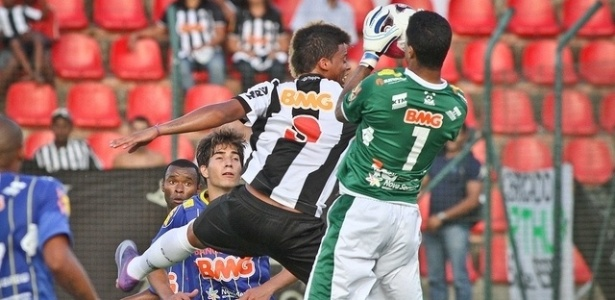 Andr pula para dividir a bola com o goleiro Raniere, do Nacional-MG