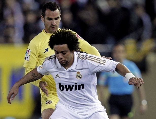 21.mar.2012 - O brasileiro Marcelo, do Real Madrid, protege a bola de Ángel López, do Villarreal, durante empate entre as equipes