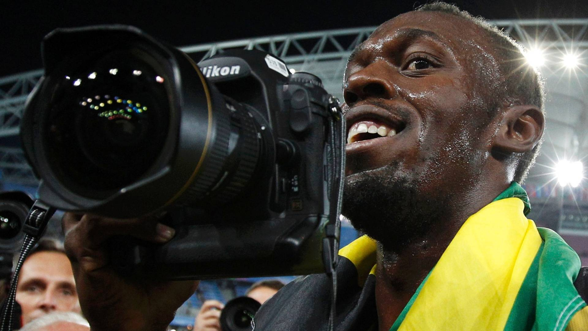 Usain Bolt pega cmera e vira fotgrafo depois de vencer os 200 m rasos no Mundial de atletismo em Daegu (03/09/2011)