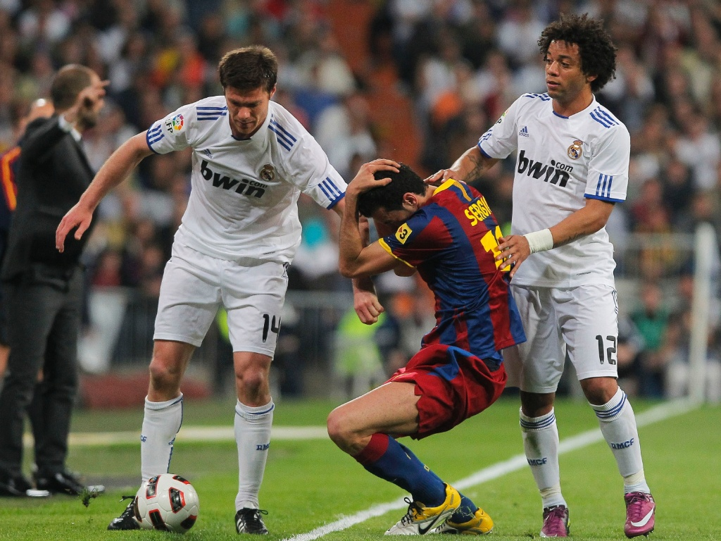 Busquets (c), do Barcelona, sofre com marcação de Xabi Alonso (e) e Marcelo, do Real Madrid (16/04/2011)