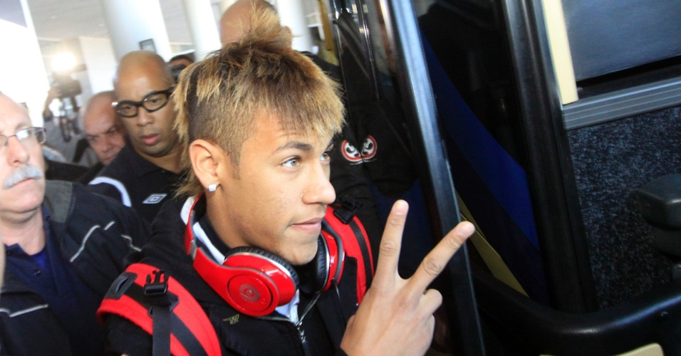 Com cabelo mais loiro do que o normal, Neymar acena ao desembarcar no Uruguai para final da Libertadores (14/06/2011)