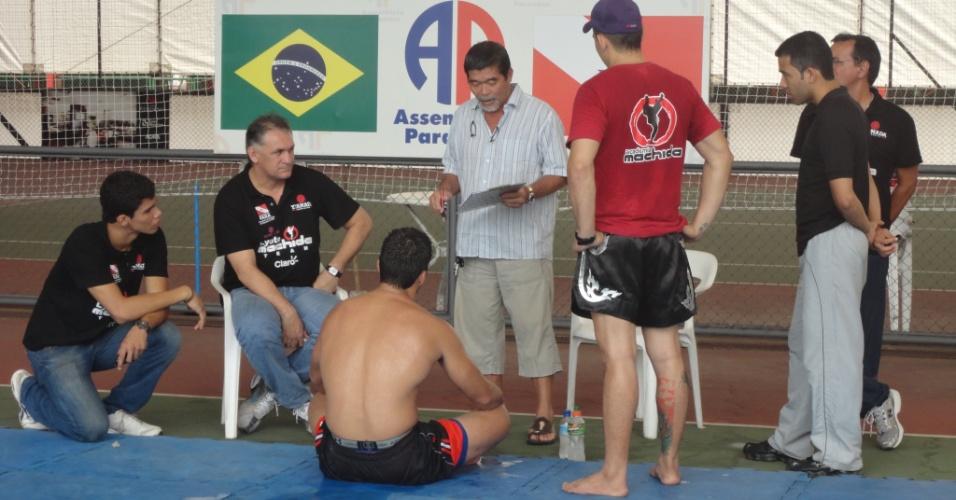 Lyoto Machida, sentado, escuta atentamente as instruções na preparação para o UFC 140, em que encara o campeão dos meio-pesados do UFC Jon Jones, para retomar o cinturão do evento