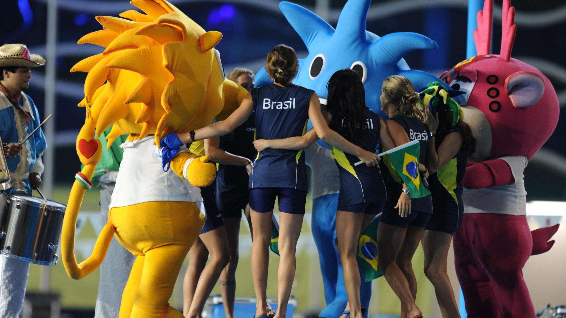 Meninas da equipe de nado sincronizado do brasil dançam com os mascotes do Pan de Guadalajara