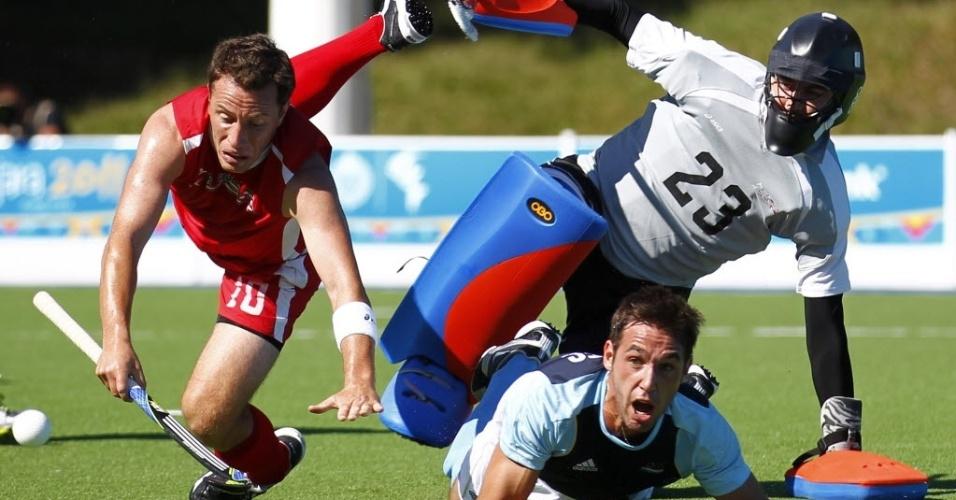 Trio do hóquei da grama vai parar no chão, em tombo durante a partida entre EUA e Argentina neste sábado (22/10/2011)
