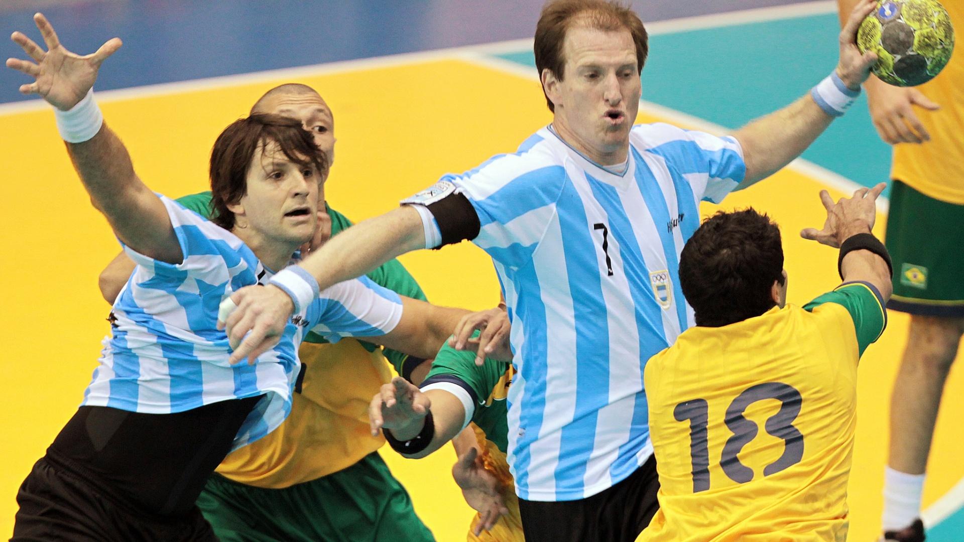 Jogador argentino tenta superar marcação de três brasileiros na decisão do handebol