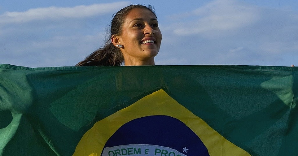 Ana Claudia Lemos sorri com a bandeira brasileira ao conquistar a medalha de ouro nos 200 m no Pan (27/10/2011)