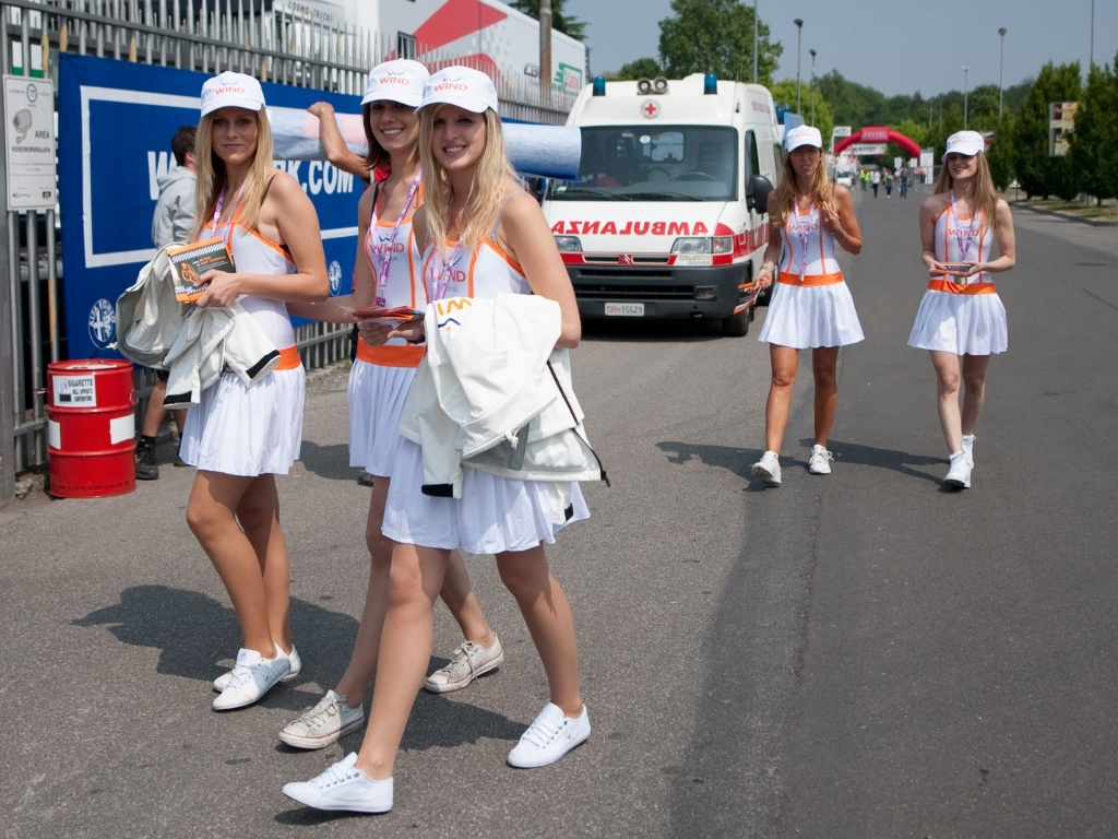 Grid girls caminham pelo paddock durante dia de treinos livres do Mundial de Superbike, em Monza, Itlia. Ambulncia j estava a postos ao fundo no caso de algum passar mal
