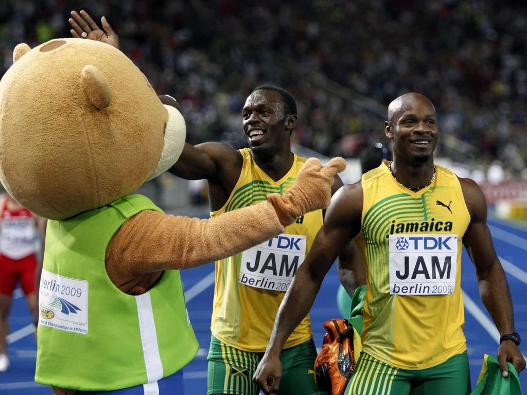 Asafa Powell (d) e Usain Bolt brincam com o mascote do Mundial de Atletismo de 2009, após vencerem o 4 x 100 m rasos na competição, em Berlim