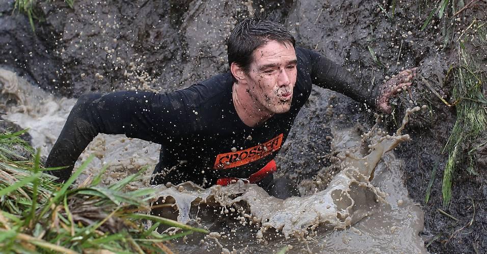 Competidor faz percurso em trincheira enlameada durante desafio de resistência realizado na Nova Zelândia