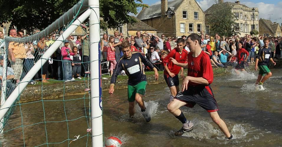 Garotos disputam partida de futebol na água na Inglaterra