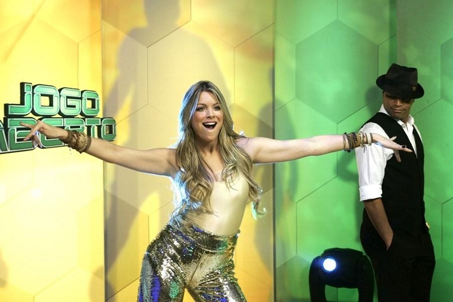 Renata Fan dança nos estúdios da Bandeirantes, observada pelo comentarista Denílson
