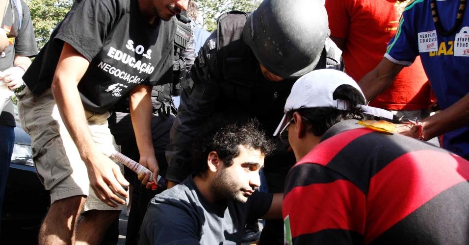 Manifestante caído é auxiliado por policial e companheiros durante protesto contra Ricardo Teixeira no Rio (30/07/2011)
