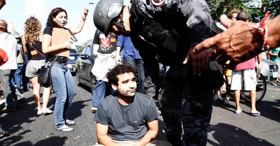Policial conversa com manifestante sentado durante protesto contra Ricardo Teixeira no Rio (30/07/2011)