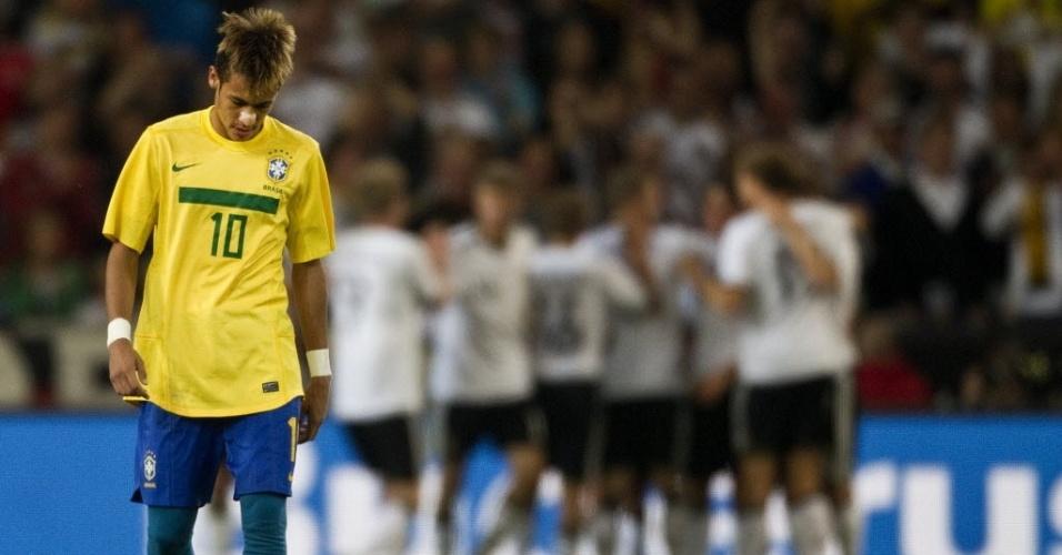 Neymar aguarda reinício do jogo cabisbaixo enquanto ao fundo alemães comemoram o gol sobre a seleção brasileira