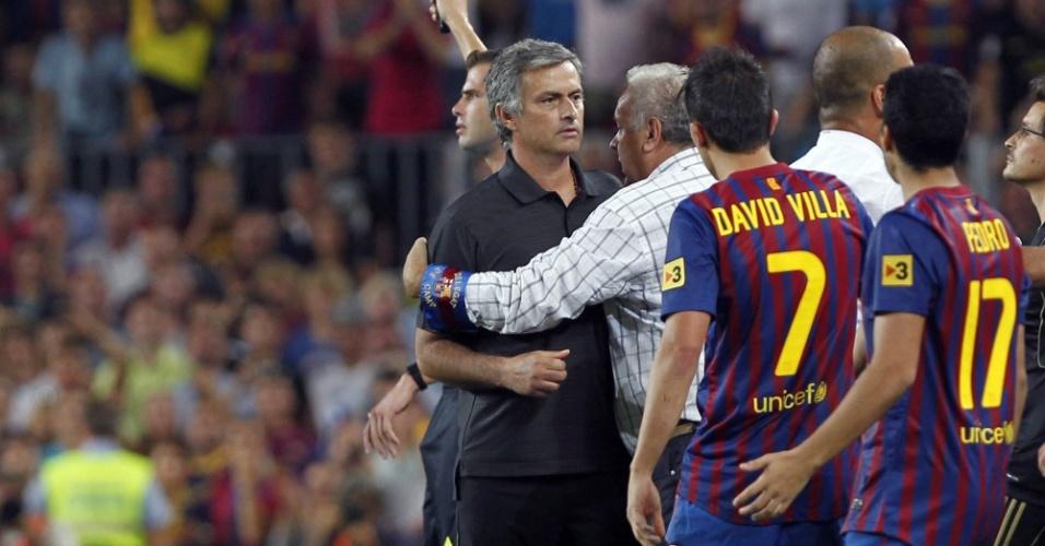 Treinador José Mourinho é contido por colegas enquanto Cesc Fabregas fica caído no chão após entrada de Marcelo