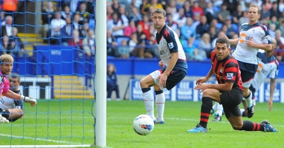 O atacante argentino Carlos Tevez, do Manchester City, aposta no olhar para empurrar a bola em direção ao gol do Bolton, pela Premier League