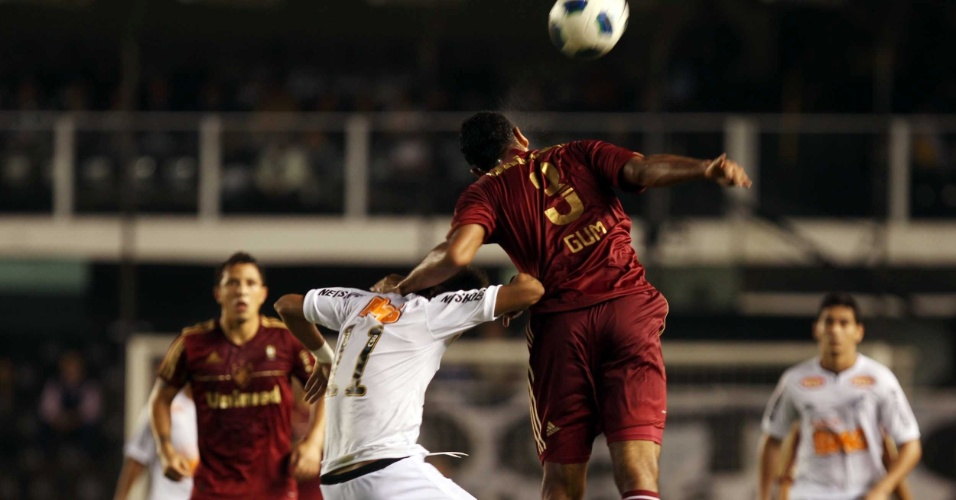 Na dividida pelo alto, o zagueiro Gum, do Fluminense, faz de tudo para segurar o santista Neymar