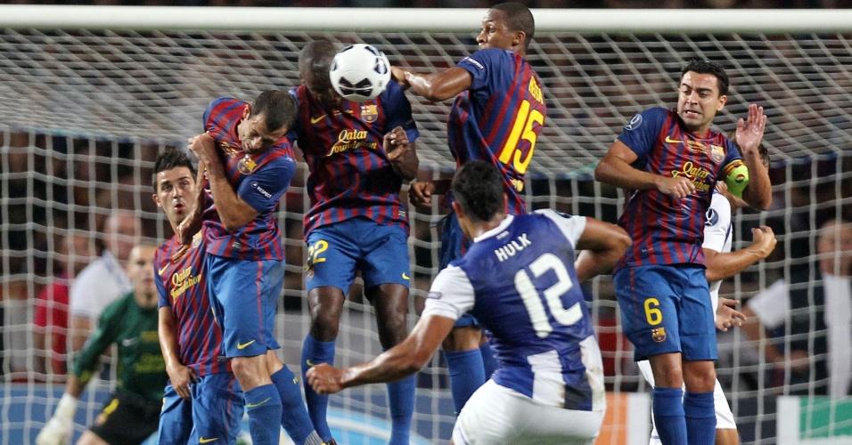 O brasileiro Hulk, do Porto, tenta fazer um gol de falta, mas a bola bate na barreira do Barcelona