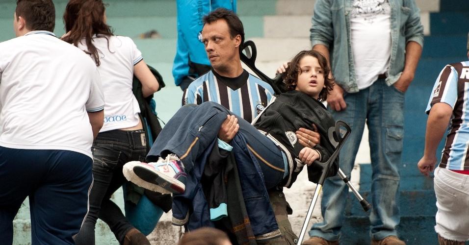 Pai carrega o filho do meio da confusão com a polícia durante Grenal no Olímpico