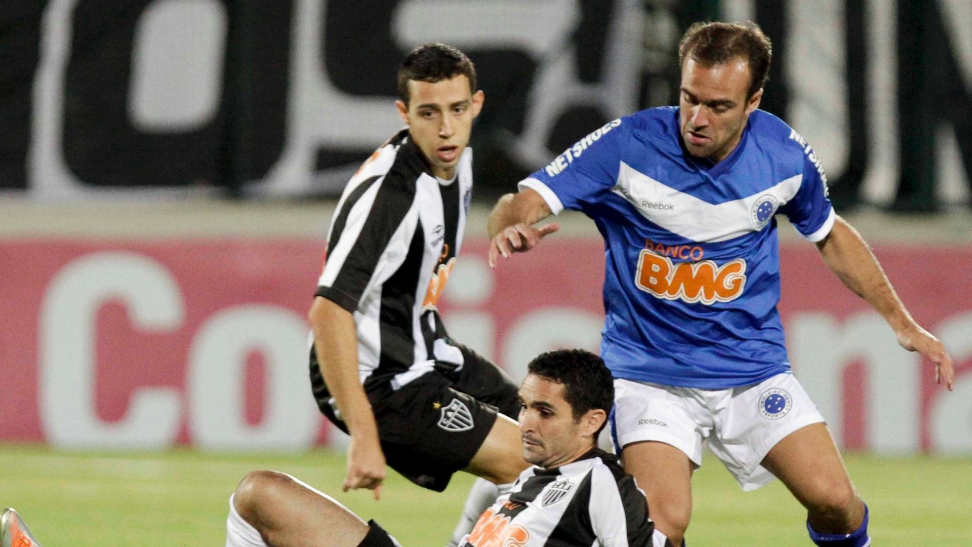 Roger (d), meia do Cruzeiro, tenta sair da marcação dos adversários atleticanos no clássico mineiro