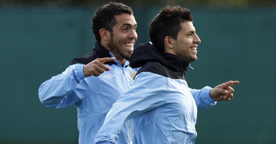 Os atacantes Sergio Agüero e Carlos Tevez dão risada durante treino do Manchester City na véspera da partida contra o Napoli pela fase de grupos da Liga dos Campeões