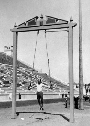 Ginasta executa exercícios nas argolas no Estádio Olímpico de Atenas