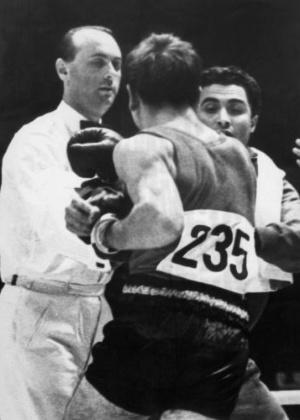 O boxeador espanhol Valentín Loren vai para cima de árbitro húngaro Josef  Serner, que o desclassificou
