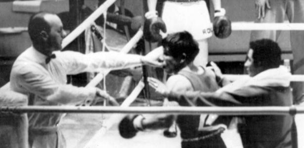 Treinador tenta conter Valentín Loren; o boxeador espanhol, após ser desclassificado, Loren tentou agredir o árbitro