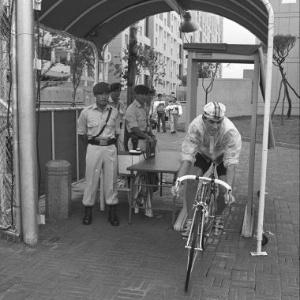 Ciclista passa de bicicleta por detector de metais na entrada da Vila Olímpica de Seul