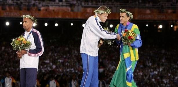 O italiano Stefano Baldini, vencedor da maratona, cumprimenta o brasileiro Vanderlei Cordeiro de Lima, medalhista de bronze, no lugar mais alto do pódio