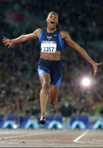 A norte-americana Marion Jones celebra va itória nos 100 m rasos, com o tempo de 10s75; anos depois, ela admitiu que fez uso de substâncias proibidas em sua vitoriosa carreira
