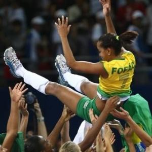A levantadora Fofão, capitã da seleção de vôlei campeã olímpica, é jogada para o alto pelas companheiras na China