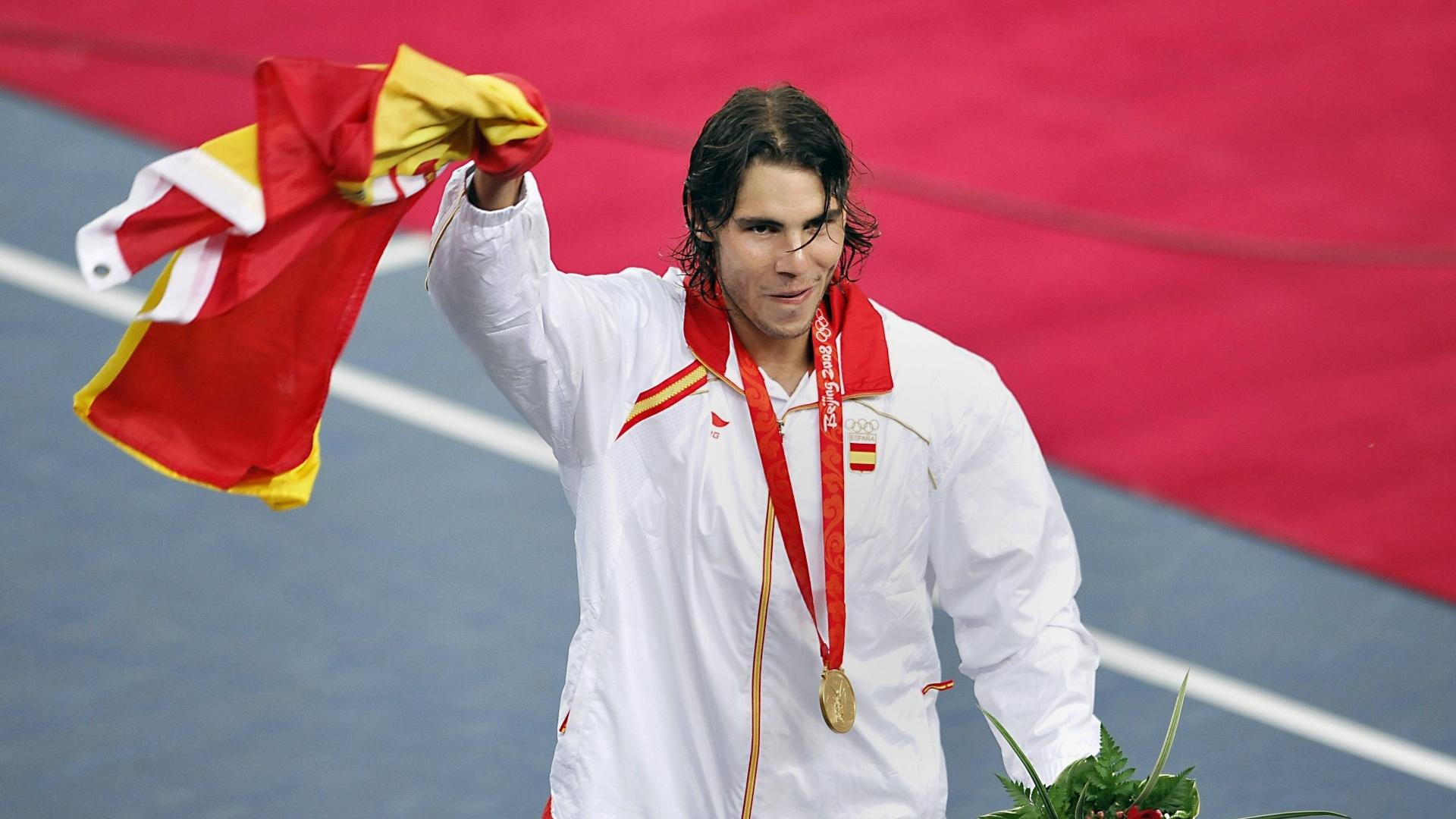 O tenista Rafael Nadal comemora com a bandeira da Espanha e sua medalha de ouro após vencer o chileno Fernando González, em Pequim