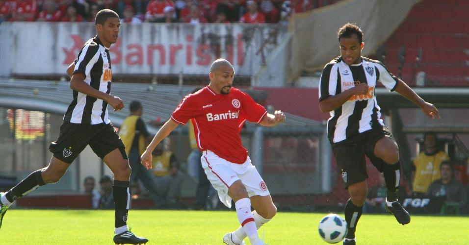 Observado por Leonardo Silva (e) e Mancini (d), Guiñazu passa a bola no Beira-Rio