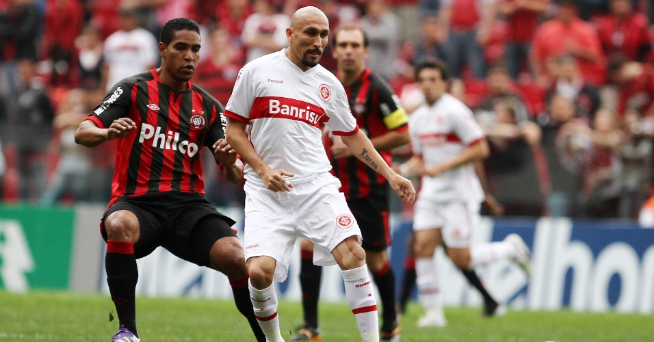Cléber Santana, do Atlético-PR, e Guiñazu, do Internacional, brigam pela posse da bola durante jogo realizado em Curitiba, neste domingo