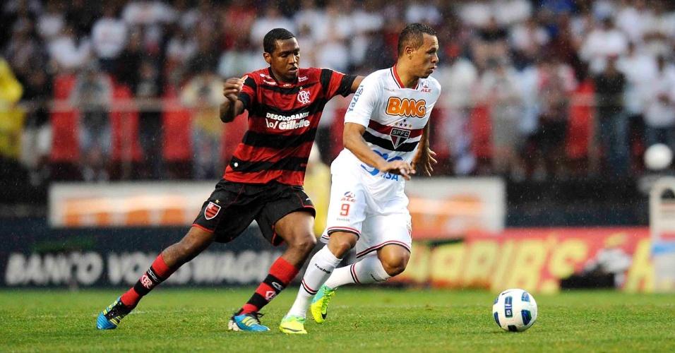 Luis Fabiano, do São Paulo, carrega a bola sob marcação de Renato Abreu, autor do gol a vitória do Flamengo