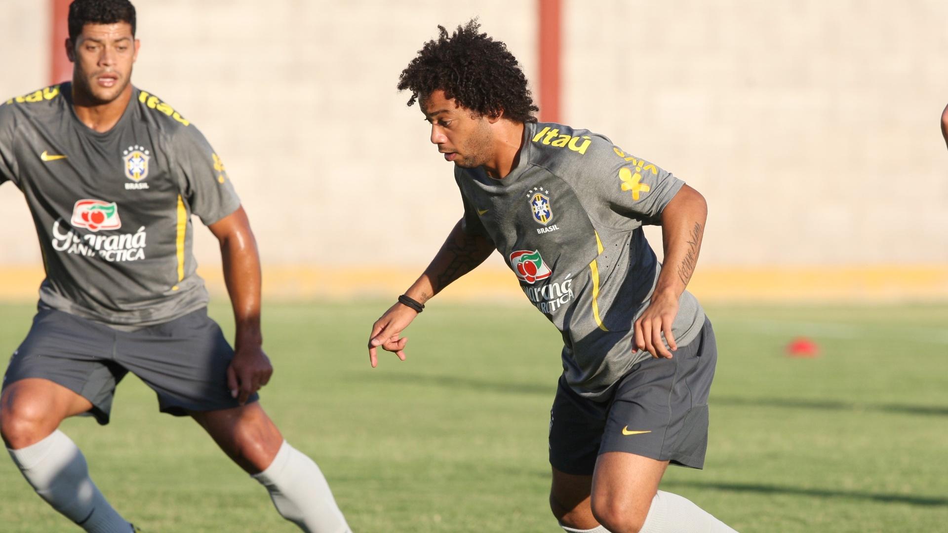 O lateral-esquerdo Marcelo tenta jogada individual enquanto é observado por Hulk, no treino do Brasil (08/10/2011)