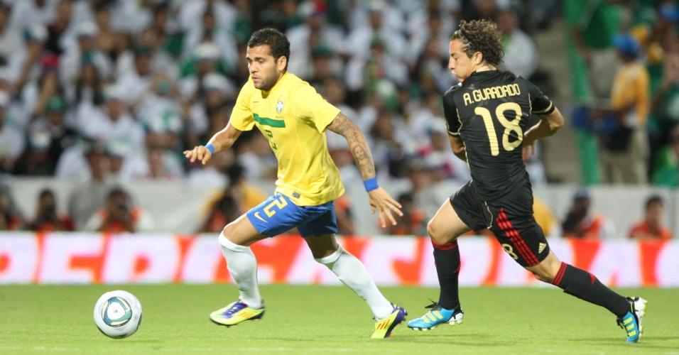 O lateral Daniel Alves ecapa da marcação do mexicano Guardado e corre pela ponta direita