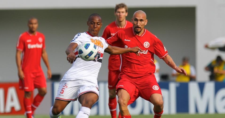 Volante Wellington, do São Paulo, disputa lance com Guiñazu, do Inter