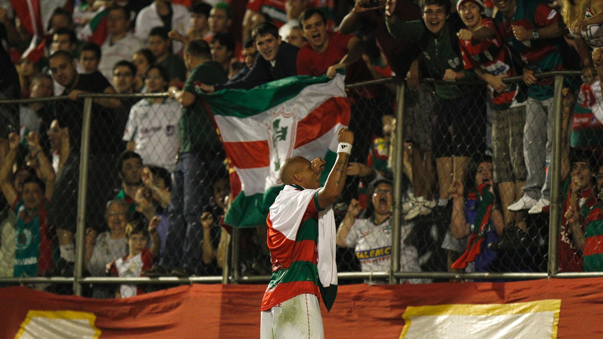 Edno carrega bandeira da Portuguesa e comemora título da Série B perto dos torcedores no Canindé