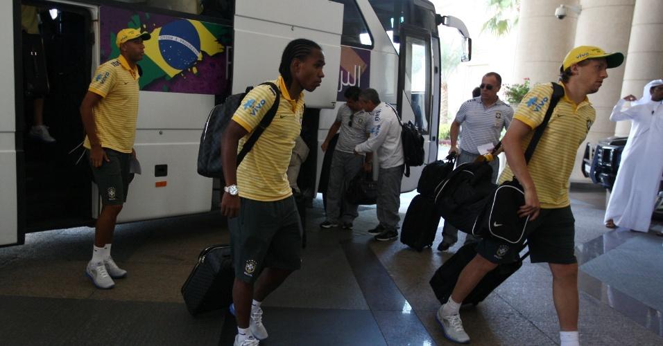 Lucas Leiva (d) puxa fila de jogadores da seleção brasileira no desembarque em Doha