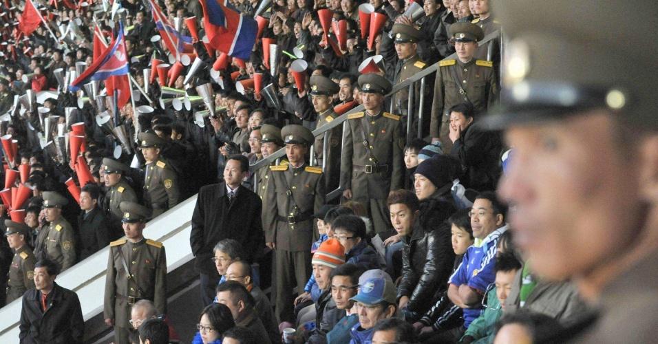 Oficiais da Coreia do Norte assistem a vitória de sua seleção ao lado dos torcedores do Japão