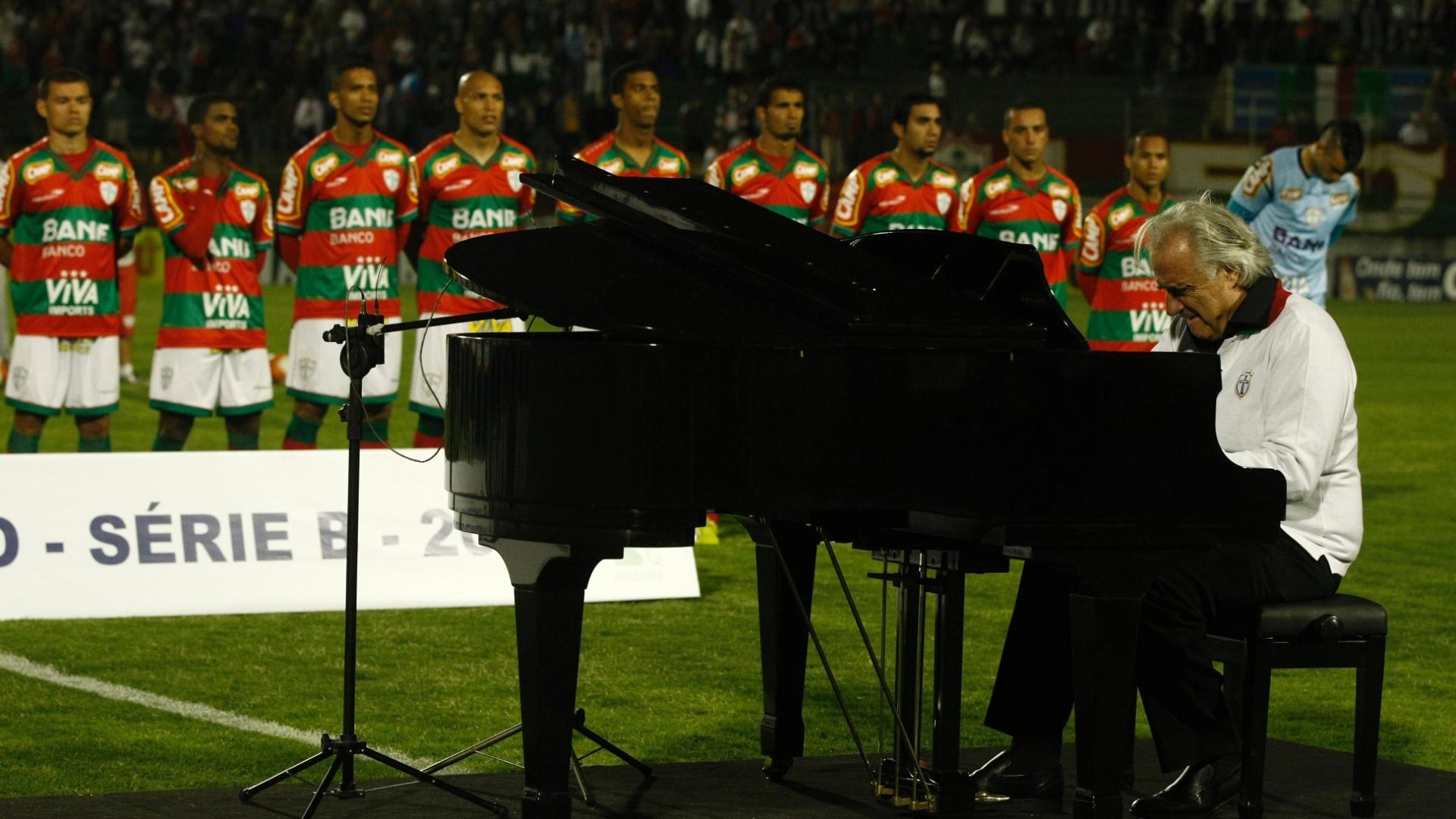 O maestro João Carlos Martins toca o hino nacional no piano antes do confronto entre Portuguesa e Duque de Caxias, pela Série B
