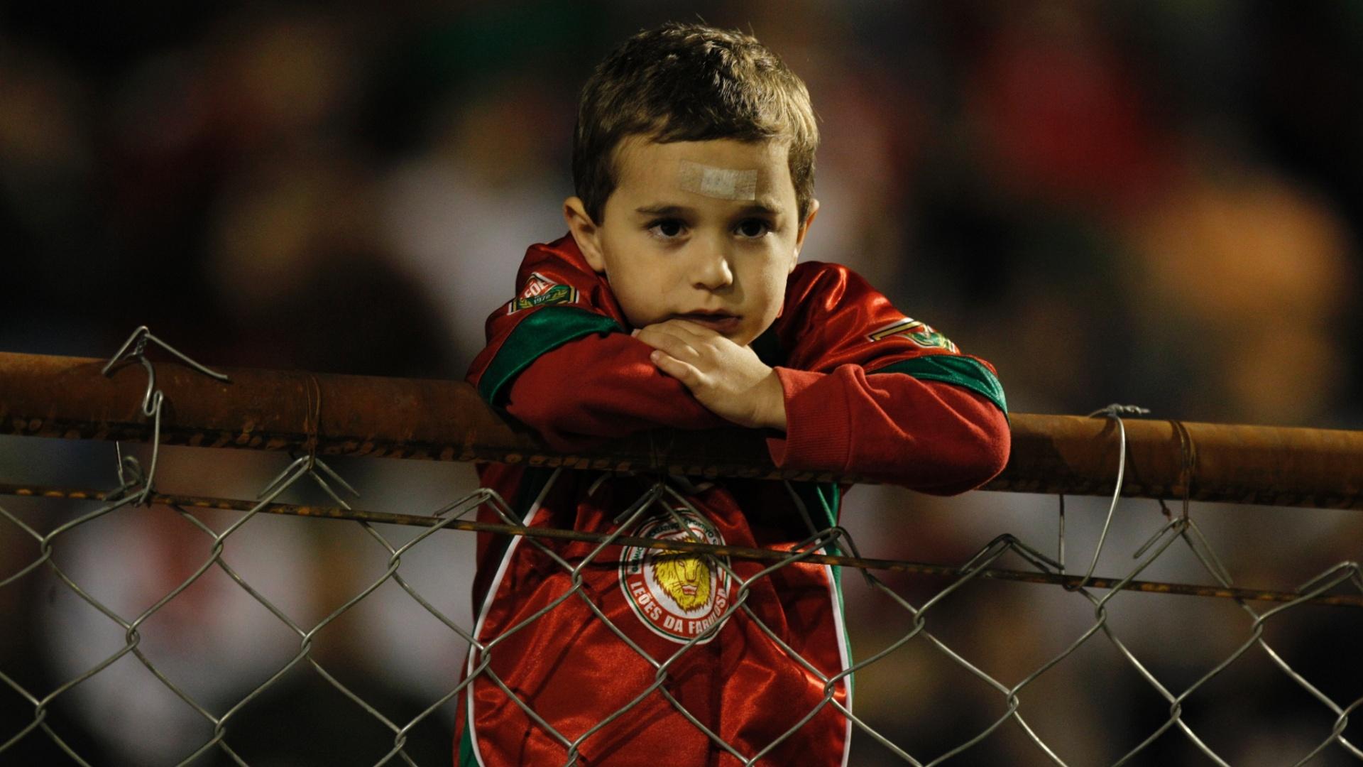 Torcedor mirim se debruça sobre alambrado do Canindé para assistir à partida entre Portuguesa e Duque de Caxias